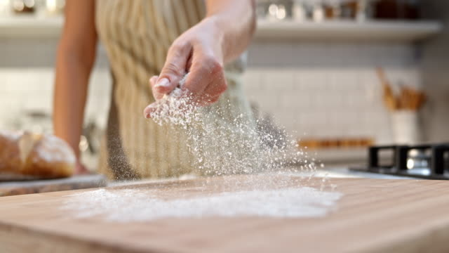 SLO MO Sprinkling the flour over wooden board with hand