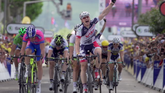 sprint and finish with fist pump by andrei greipel winner of stage 4 of 2012 tour de france - ツール・ド・フランス点の映像素材/bロール