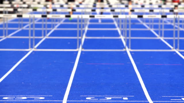 sprint hurdle race for men on blue track - athleticism stock videos and b-roll footage