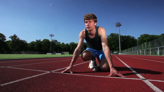 stockvideo's en b-roll-footage met sprinter at starting line - concentratie