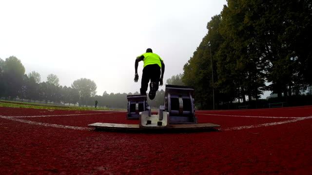 stockvideo's en b-roll-footage met sprinter runs off the starting block - pjphoto69
