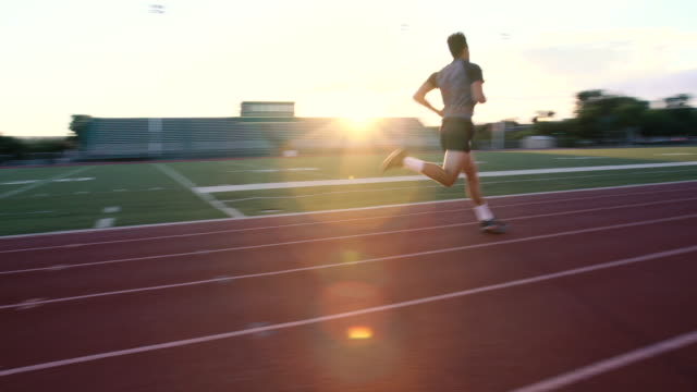 sprinting on the track at sunset - sports track stock videos and b-roll footage