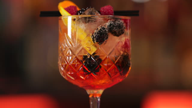 aperol spritz cocktail with dark fruit garnish - cocktail stock videos and b-roll footage
