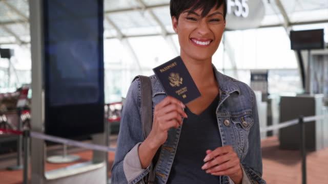 vídeos y material grabado en eventos de stock de spunky african woman at airport poses confidently with passport - sólo mujeres jóvenes