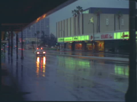 ts lapd squad cars with lights flashing speeding down rainy business street at night / los angeles, california, united states - 1960 stock-videos und b-roll-filmmaterial