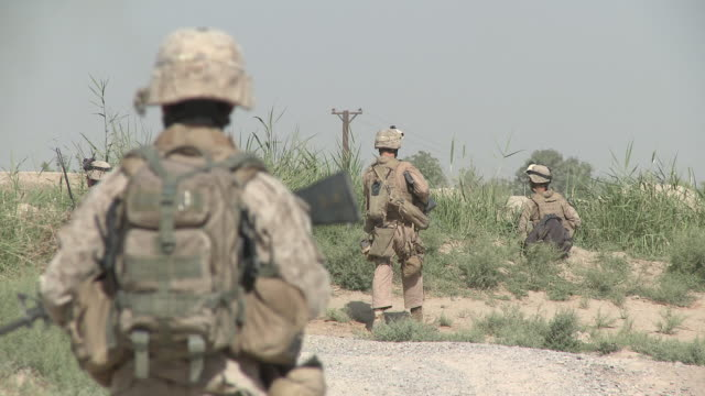 A squad of U.S. Marines patrols as a Humvee passes nearby.