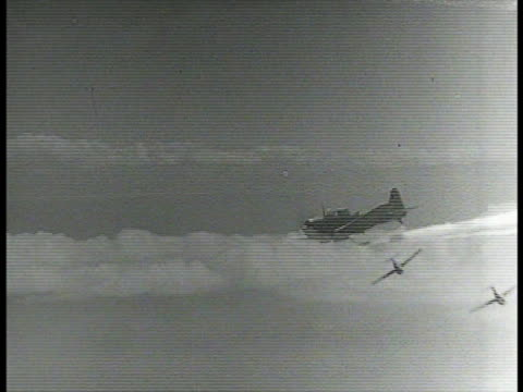 Squad of US single engine fighter airplanes diving WS Airplane diving laying smoke screen over waters XWS Airplanes flying through smoke screen at...