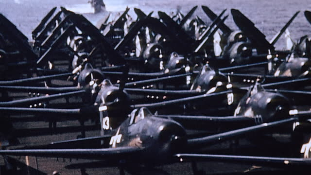 squadron of fighters on flight deck of uss essex warming up engines some with wings folded and f6f hellcat taxiing past damaged sb2c helldiver - battle of iwo jima stock videos and b-roll footage