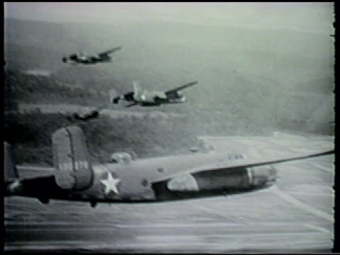 squadron of north american b-25 mitchell bomber aircrafts flying. flying low, bombs exploding across landscape, river. wwii, world war ii, pacific... - world war ii video stock e b–roll