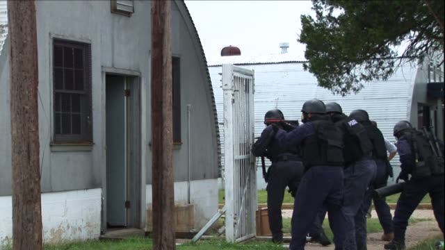 a squadron of police officers enter a home with a meth lab using a battering ram. - police force stock-videos und b-roll-filmmaterial