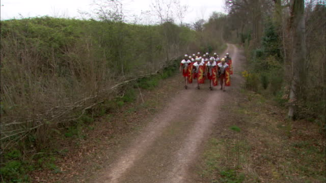 vídeos de stock e filmes b-roll de squads of roman soldiers march along a country trail. - traditional helmet