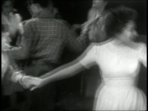 stockvideo's en b-roll-footage met 1946 montage square dancers join hands in a circle as fiddler plays along - 1946