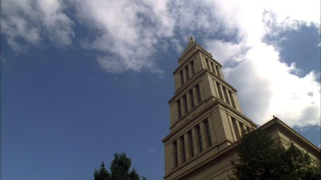 stockvideo's en b-roll-footage met la square multi-level tower with clouds passing overhead - kerktoren