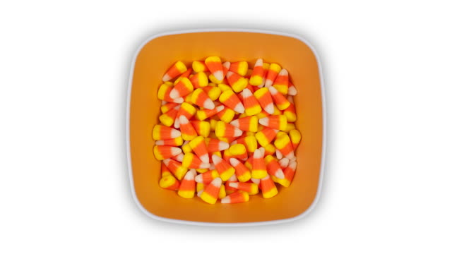 a square orange dish filling with candy corn and emptying again, time lapse - artbeats stock videos & royalty-free footage