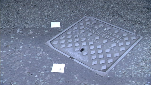 Square shaped manhole on street w/ City Centre Manchester letterings unidentifiable vehicles passing over sign