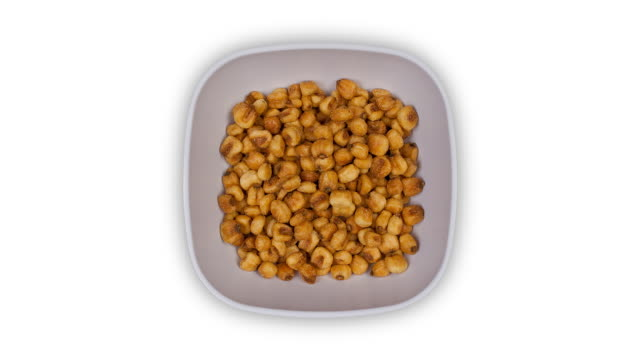 a square white dish filling with cornnuts and emptying again, time lapse - cibo cotto video stock e b–roll