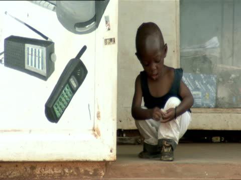 ms tu squatting little boy rolls up piece of tissues, stands and runs into doorway / nyamirambo, kigali, rwanda - nur jungen stock-videos und b-roll-filmmaterial