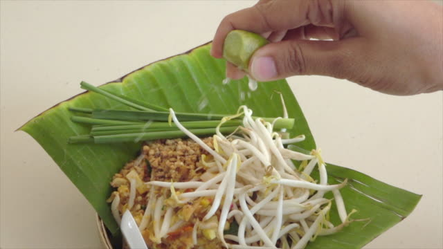 squeeze lemon on pad thai noodle slow motion - peanut food stock videos & royalty-free footage