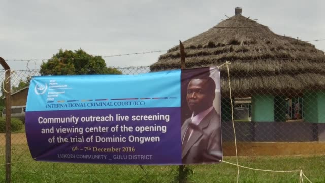 squeezed onto dilapidated wooden school benches villagers in northern uganda watched the trial of dominic ongwen at the international criminal court - international criminal court stock videos and b-roll footage