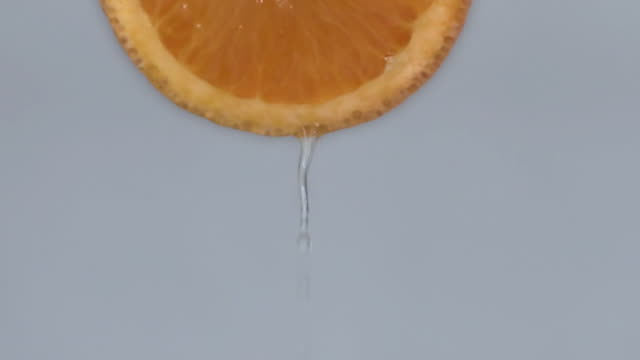 squeezing juice from an orange slice - silhouette - juicy stock videos & royalty-free footage