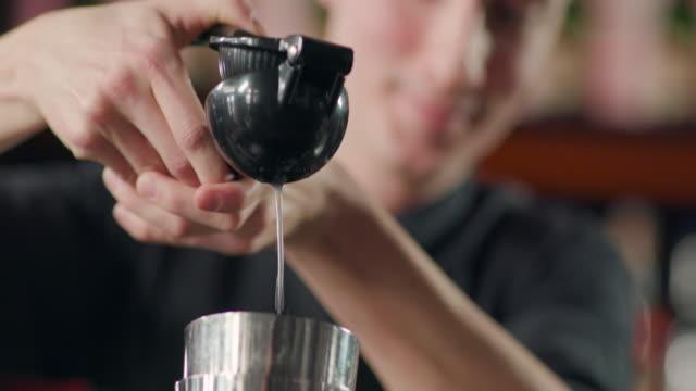 vidéos et rushes de presser le jus de citron dans le shaker - shaker
