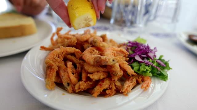 vidéos et rushes de presser le citron sur les crevettes. déjeuner familial. fruits de mer - presser