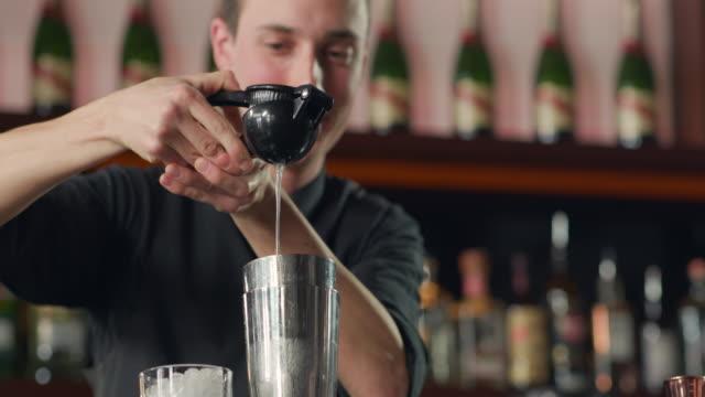 vidéos et rushes de presser le citron avec le presse-pression dans le shaker - shaker