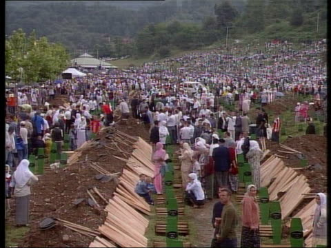 crowds of people attending funeral ceremony gather near area dug up for coffins - srebrenica stock videos and b-roll footage
