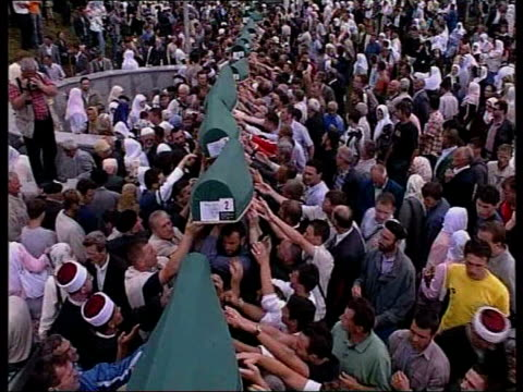 un rules serbia not directly to blame lib srebrenica potocari ext high angle view of green caskets laid out green caskets passed over people's heads... - islam bildbanksvideor och videomaterial från bakom kulisserna