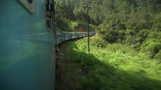 sri lanka famous and iconic train to ella. young woman legs hanging from the door - sri lanka stock-videos und b-roll-filmmaterial