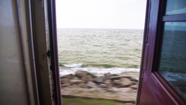 sri lanka train to colombo. beach landscape - colonial stock-videos und b-roll-filmmaterial