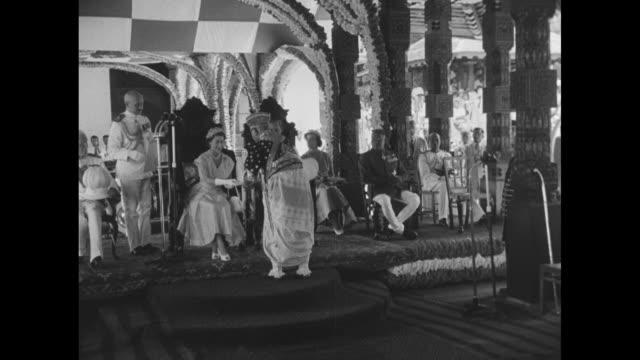 stockvideo's en b-roll-footage met cu sri lankan man in ceremonial dress / ls chiefs seated in audience hall / ms chiefs greet elizabeth ii and prince philip with handshakes / fs side... - sri lankaanse cultuur