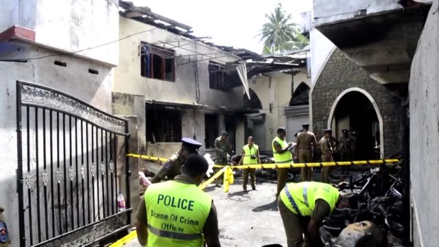 sri lankan security personnel and police investigators look through debris outside zion church following an explosion in batticaloa in eastern sri... - sri lanka stock videos & royalty-free footage