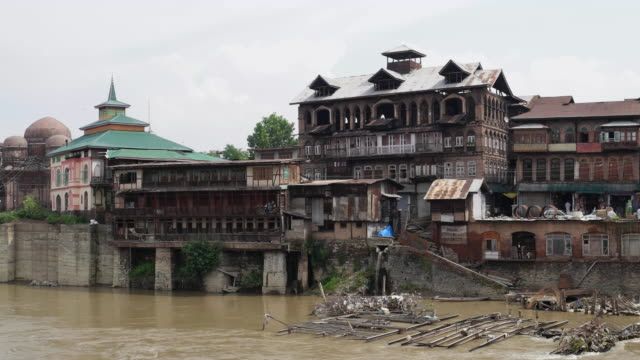 Srinagar old city view with mosques, temples, burned and abandoned houses, as seen from a bridge on the Jhelum river