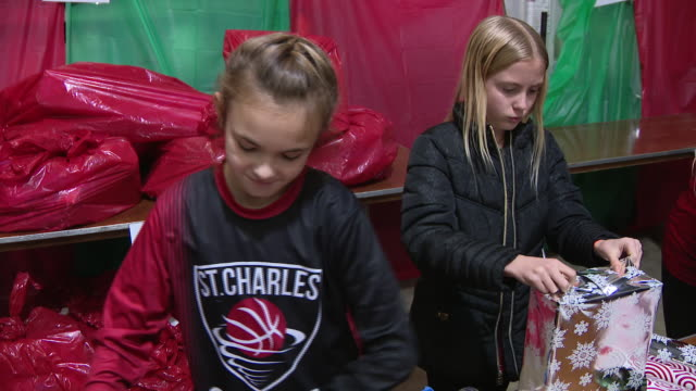 wgn st charles il us volunteers gathered to wrap christmas presents for families in need on tuesday december 10 2019 - sharing stock videos & royalty-free footage