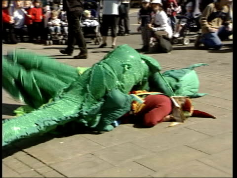 St George's Day English national pride ITN Wiltshire Salisbury EXT Jester in dragon costume battling St George in reenactment of slaying to celebrate...