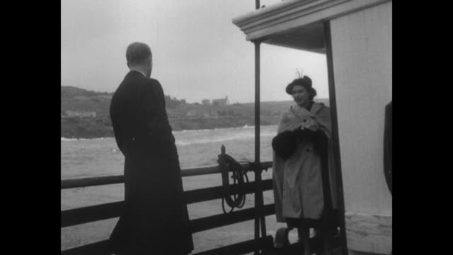 WS St John's Newfoundland [exact month/day not known] / Princess Elizabeth boards ferry Maneco wrapped in raincoat Philip Duke of Edinburgh follows /...