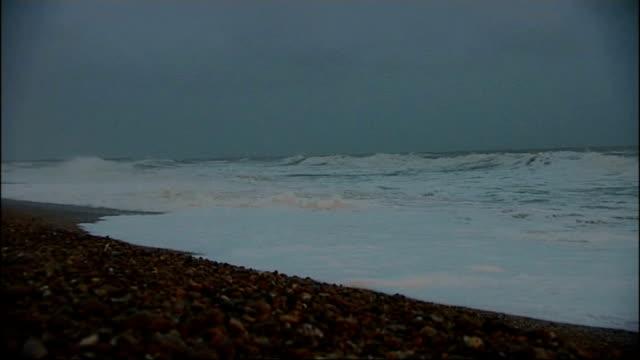 st jude storm approaches: rough seas at brighton; england: east sussex: brighton: ext / dusk various shots of illuminated brighton pier with large... - ブライトン パレスピア点の映像素材/bロール