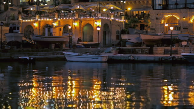 WS St. Julian's Bay waterfront illuminated at dusk / Malta