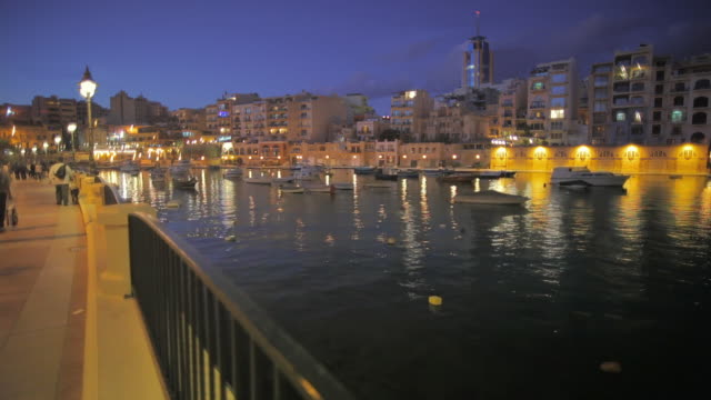 ws st. julian's bay waterfront illuminated at dusk / malta - establishing shot点の映像素材/bロール