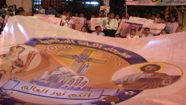 vídeos de stock e filmes b-roll de st. mark's festival. on a cloth banner with images of a coptic cross, st. mark's coptic cathedral, pope shenouda iii, and jesus. copts make up 10-15... - cathedral