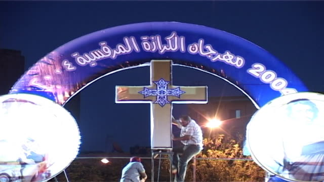 st mark's festival ls on men adjusting a three dimensional lit coptic cross in the middle of a round festival banner - three dimensional stock videos & royalty-free footage