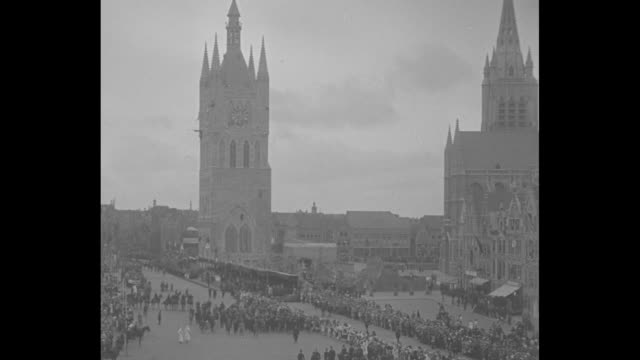 WV St Martin's Cathedral on right and Cloth Hall belfry on left crowd in square to left of belfry / shot from ground of belfry pan down to crowd in...