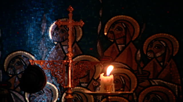 st mary orthodox church view of a lit candle placed before a gilded cross and a mosaic mural of images of jesus and the apostles - christianity stock videos & royalty-free footage