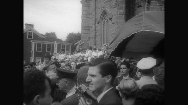 stockvideo's en b-roll-footage met ext st mary's church in newport / large crowd wait along sidewalk / bridesmaids exit car / police hold back crowd as jacqueline kennedy onassis steps... - jacqueline kennedy