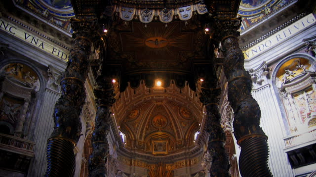 St. Peter's Basilica in Vatican City, Italy. Tilting up from the main Papal altar, past Bernini's bronze baldacchino canopy, to see the dome high above, as the sunlight streams in.