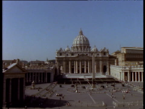 st peter's basilica including piazza obelisk and people milling around the square vatican city - monumento video stock e b–roll