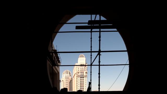st. regis hotel, doha, qatar. view through an archway under construction of the towers of the five-star st. regis hotel in west bay. - b roll bildbanksvideor och videomaterial från bakom kulisserna
