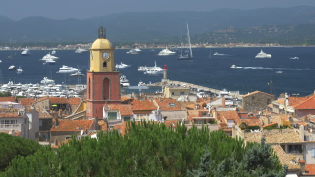 vídeos y material grabado en eventos de stock de st tropez with church bell tower and yachts in the distance.4k - var