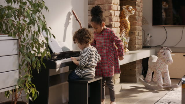 fs, stabilised handheld - mixed race siblings playing together on piano - sister stock videos & royalty-free footage